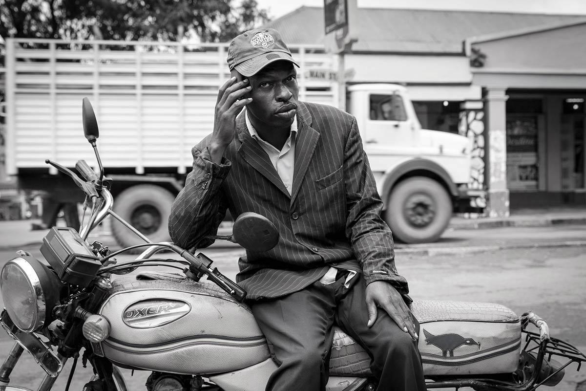 Ugandan man receiving a call: Media & Communication