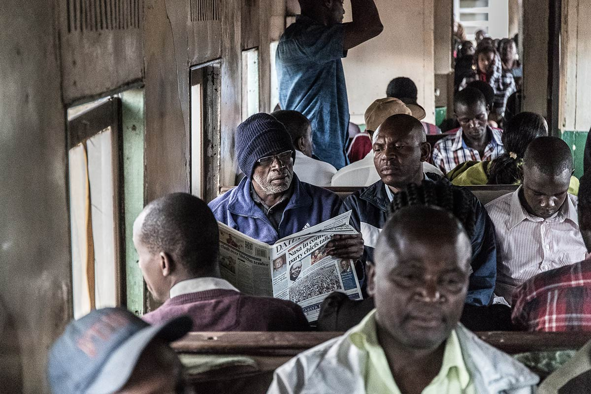 Media & Communication in Uganda: Man reading newspaper on a train